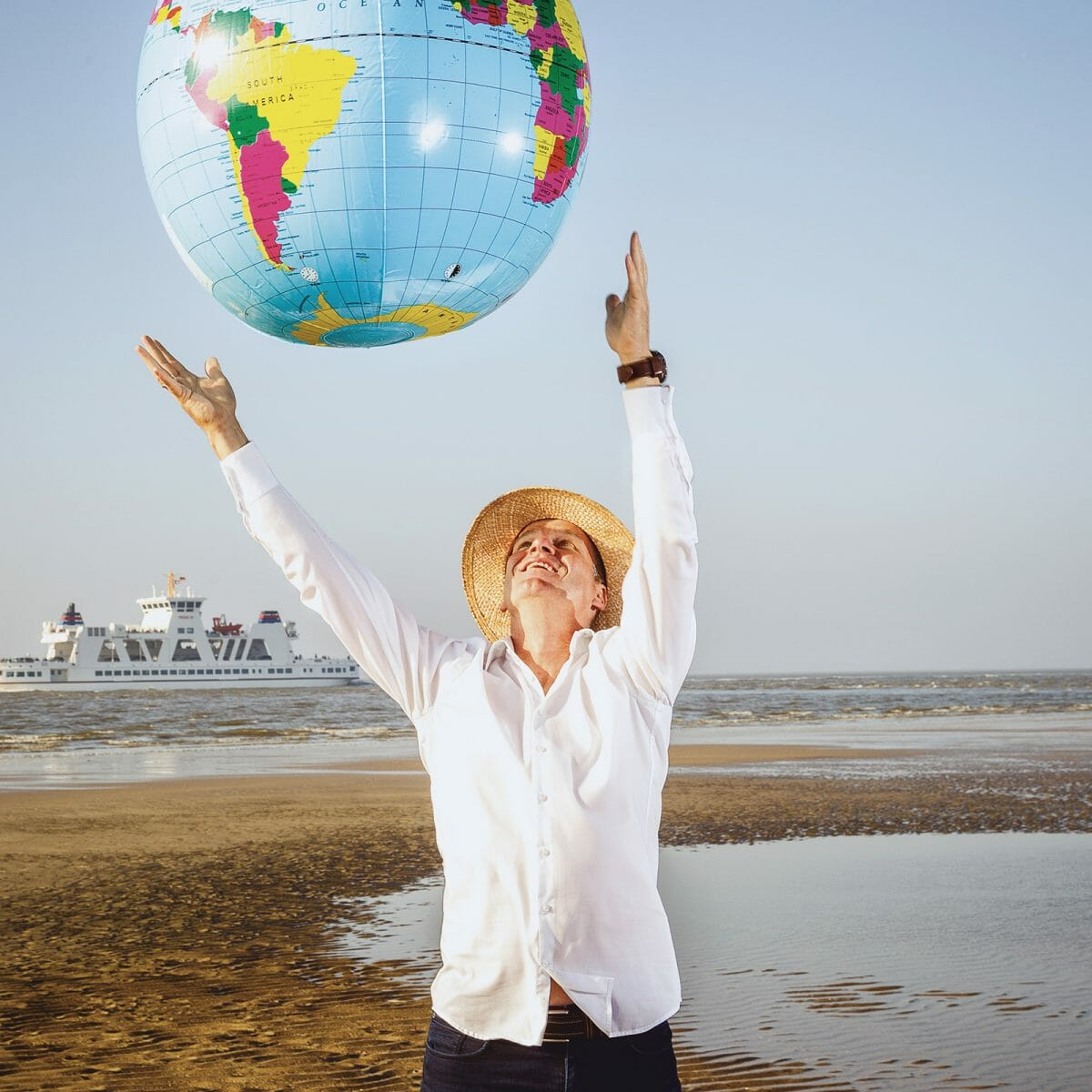 Der Inhaber des Norderneyer Reisebüros mit einer riesigen Weltkugel am Weststrand von Norderney.
