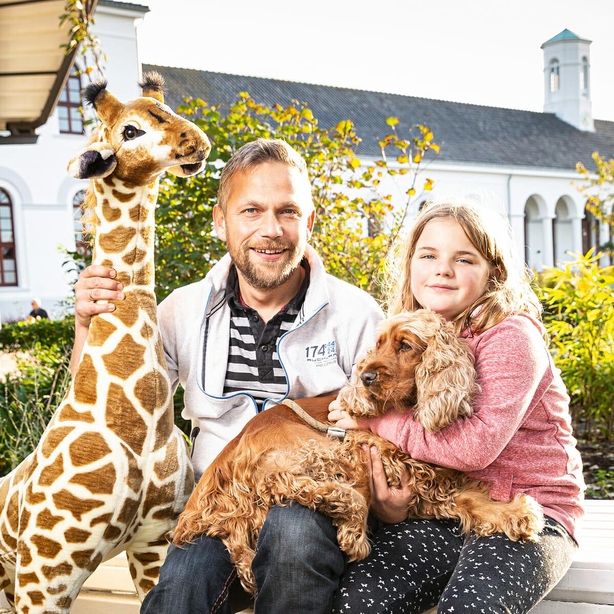 Spielwarenhändler Kai Schnieder mit Tochter, Hund und einem riesigen Stofftier vor dem Norderneyer Conversationshaus am Kurplatz