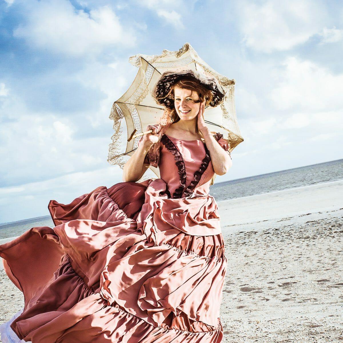 Die Insulanerin Swana Dinkla am Weststrand in einem originalgetreu nachgeschneiderten Kleid aus dem Bademuseum Norderney.